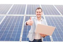 Άτομο που στέκεται κοντά στα ηλιακά πλαίσια, που κρατά το lap-top, που χαμογελά και που παρουσιάζει αντίχειρα του μπροστά από τον στοκ εικόνες με δικαίωμα ελεύθερης χρήσης