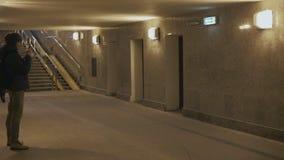 Άτομο που στέκεται με ένα smartphone στην υπόγεια διάβαση φιλμ μικρού μήκους