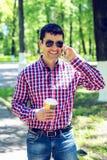 Άτομο που στέκεται με τον καφέ ή το τσάι, που μιλά στο τηλέφωνο, το καλοκαίρι στα γυαλιά και ένα πουκάμισο στα ξύλα υπαίθρια Στοκ φωτογραφία με δικαίωμα ελεύθερης χρήσης