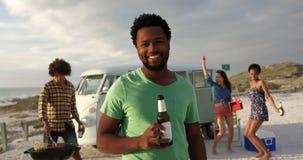 Άτομο που στέκεται με το μπουκάλι μπύρας στην παραλία 4k απόθεμα βίντεο