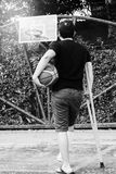 Άτομο που στέκεται με το σπασμένο πόδι στο ασβεστοκονίαμα χυτό χρησιμοποιώντας τα δεκανίκια Στοκ Εικόνες