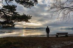 Άτομο που στέκεται μόνο δίπλα σε έναν πάγκο θαλασσίως, εξετάζοντας το ήρεμο νερό και την υδρονέφωση και την ομίχλη Hamresanden, K στοκ εικόνες