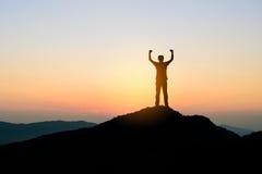 Άτομο που στέκεται πάνω από το βουνό στο υπόβαθρο ηλιοβασιλέματος, σκιαγραφία Στοκ εικόνες με δικαίωμα ελεύθερης χρήσης