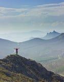 Άτομο που στέκεται σε έναν απότομο βράχο στα βουνά με τα χέρια επάνω Στοκ Φωτογραφίες