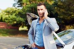 Άτομο που στέκεται σε ένα σπασμένες αυτοκίνητο και μια κλήση Στοκ Φωτογραφία