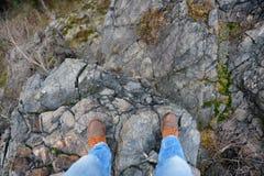 Άτομο που στέκεται στην άκρη ενός απότομου βράχου Στοκ Φωτογραφία