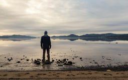 Άτομο που στέκεται στην παραλία, εξετάζοντας την ήρεμη θάλασσα και την υδρονέφωση και την ομίχλη Hamresanden, Kristiansand, Νορβη στοκ φωτογραφίες