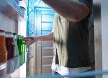 Άτομο που στέκεται στη ανοιχτή πόρτα ενός ψυγείου στοκ εικόνες
