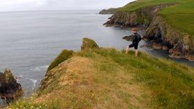 Άτομο που στέκεται στο βουνό απότομων βράχων με το χέρι του στο ισχίο 4k απόθεμα βίντεο