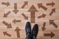 Άτομο που στέκεται στο ξύλινο πάτωμα με τα βέλη που δείχνουν στις διαφορετικές κατευθύνσεις Έννοια της επιλογής στοκ εικόνες με δικαίωμα ελεύθερης χρήσης