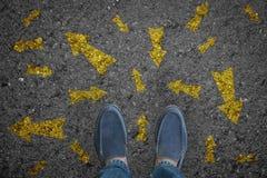 Άτομο που στέκεται στο δρόμο με πολλές επιλογές ή την κίνηση βελών κατεύθυνσης Στοκ φωτογραφία με δικαίωμα ελεύθερης χρήσης