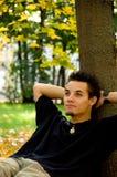 Άτομο που στηρίζεται κάτω από ένα δέντρο Στοκ Εικόνα