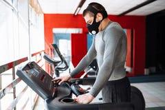 Άτομο που στηρίζεται πριν από την επόμενη φυλή, που κάνει τον αθλητισμό, σε μια μάσκα κατάρτισης για την αναπνοή treadmill, κατάρ στοκ φωτογραφία
