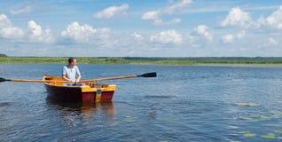 Άτομο που στηρίζεται στη λίμνη, που οδηγά μια βάρκα με τα κουπιά, υπάρχει μια θέση για την επιγραφή στοκ εικόνες
