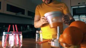 Άτομο που συμπιέζει το φρέσκο χυμό από πορτοκάλι με ένα juicer απόθεμα βίντεο