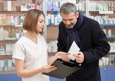 Άτομο που συσκέπτεται με το θηλυκό φαρμακοποιό στο φαρμακείο στοκ εικόνες