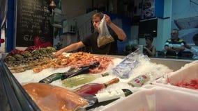 Άτομο που συλλέγει τις μεγάλες γαρίδες στη πλαστική τσάντα στην αγορά ψαριών απόθεμα βίντεο