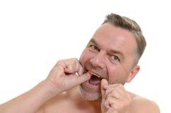 Άτομο που τα δόντια του με το οδοντικό νήμα στοκ εικόνες