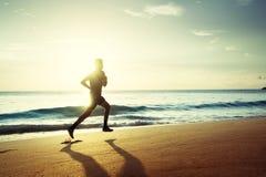 Άτομο που τρέχει στην τροπική παραλία στο ηλιοβασίλεμα Στοκ εικόνα με δικαίωμα ελεύθερης χρήσης