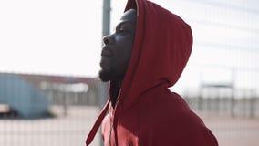 Άτομο που τρέχει στο ηλιοβασίλεμα στην πόλη Αρσενικός δρομέας αθλητών αφροαμερικάνων που φορά το κόκκινο hoodie Να ασκήσει υπαίθρ απόθεμα βίντεο