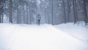 Άτομο που τρέχει στο χιονισμένο χειμερινό δρόμο στο δάσος απόθεμα βίντεο