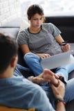 Άτομο που τρίβει τη φίλη που χρησιμοποιεί τον υπολογιστή στον καναπέ στοκ εικόνες με δικαίωμα ελεύθερης χρήσης