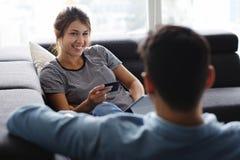 Άτομο που τρίβει τη φίλη που χρησιμοποιεί τον υπολογιστή στον καναπέ στοκ εικόνα