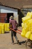 Άτομο που τραβά τη δίτροχο χειράμαξα που φορτώνεται με τα πλαστικά βαρέλια στοκ φωτογραφία με δικαίωμα ελεύθερης χρήσης