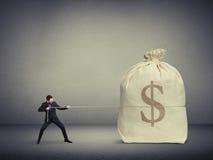 Άτομο που τραβά το σχοινί μια μεγάλη τσάντα των χρημάτων στοκ φωτογραφίες