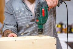 Άτομο που τρυπά μια ξύλινη κινηματογράφηση σε πρώτο πλάνο ραφιών με τρυπάνι στοκ φωτογραφίες με δικαίωμα ελεύθερης χρήσης