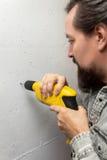 Άτομο που τρυπά μια τρύπα με μια μηχανή τρυπανιών στο χέρι του με τρυπάνι Στοκ εικόνα με δικαίωμα ελεύθερης χρήσης