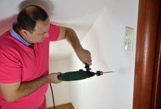 Άτομο που τρυπά μια τρύπα με τρυπάνι Στοκ εικόνα με δικαίωμα ελεύθερης χρήσης