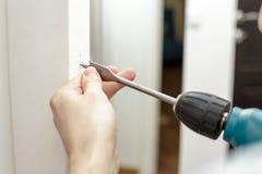 Άτομο που τρυπά μια τρύπα σε μια ξύλινη πόρτα με τρυπάνι Στοκ Εικόνες
