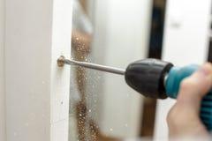 Άτομο που τρυπά μια τρύπα σε μια ξύλινη πόρτα με τρυπάνι Στοκ φωτογραφία με δικαίωμα ελεύθερης χρήσης