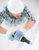 Άτομο που τρυπά τον τοίχο με τρυπάνι Στοκ εικόνα με δικαίωμα ελεύθερης χρήσης