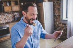 Άτομο που τρώει τα δημητριακά και που χρησιμοποιεί την ψηφιακή ταμπλέτα στοκ φωτογραφία