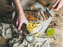 Άτομο που τρώει τα πλευρά χοιρινού κρέατος και που χύνει σκοτεινή την μπύρα στο γυαλί Στοκ Φωτογραφία