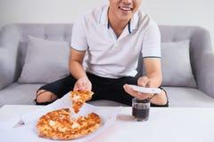 Άτομο που τρώει την πίτσα που έχει μια take-$l*away στο σπίτι χαλαρώνοντας στήριξη στοκ εικόνες