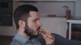 Άτομο που τρώει την πίτσα και που κάθεται στον καναπέ στο σπίτι φιλμ μικρού μήκους