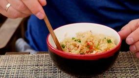 Άτομο που τρώει το ρύζι με τα λαχανικά στα κινέζικα reastaurant φιλμ μικρού μήκους