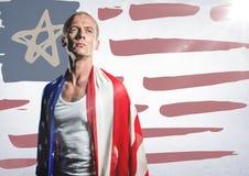 Άτομο που τυλίγονται στη αμερικανική σημαία ενάντια συρμένη στη χέρι αμερικανική σημαία και λευκός τοίχος με τη φλόγα Στοκ Εικόνα