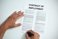 Άτομο που υπογράφει μια σύμβαση της απασχόλησης Στοκ Φωτογραφία