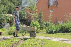 Άτομο που φέρνει wheelbarrow στο χωριό Στοκ Φωτογραφίες