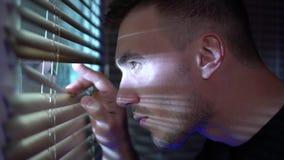 Άτομο που φαίνεται έξω το παράθυρο μέσω των τυφλών στην οδό, κατασκόπευση απόθεμα βίντεο
