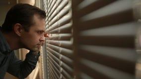 Άτομο που φαίνεται έξω το παράθυρο μέσω των τυφλών στην οδό, κατασκόπευση πιθανός απόθεμα βίντεο