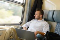 Άτομο που φαίνεται έξω το lap-top παραθύρων τραίνων Στοκ Εικόνες
