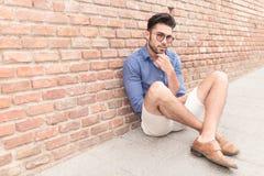 Άτομο που φαίνεται σκεπτικό καθμένος στο πεζοδρόμιο Στοκ εικόνα με δικαίωμα ελεύθερης χρήσης