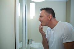 Άτομο που φαίνεται το πρόσωπό του στον καθρέφτη μετά από να ξυρίσει στοκ εικόνα