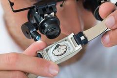 Άτομο που φαίνεται Wristwatch με Loupe Στοκ φωτογραφία με δικαίωμα ελεύθερης χρήσης