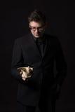 Άτομο που φορά ένα μαύρο κοστούμι που κρατά ένα ζωικό κρανίο και που σκέφτεται για τη ζωή στη γη Στοκ Εικόνα